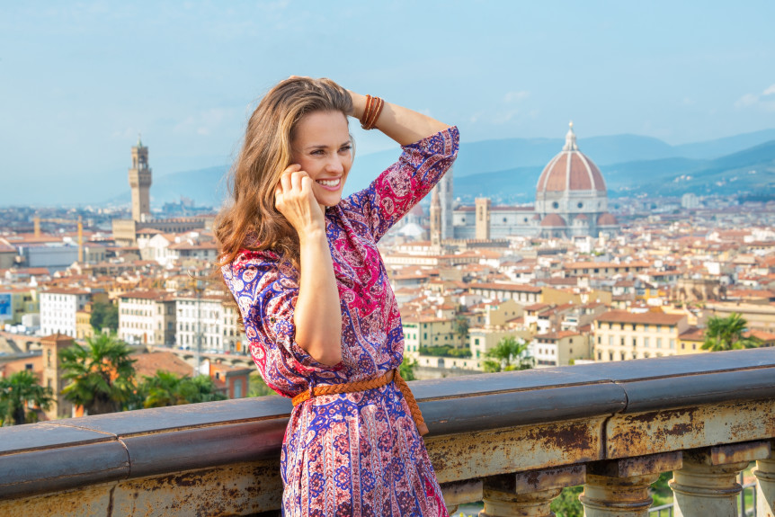 Happy young woman talking cell phone against panoramic view of florence italy