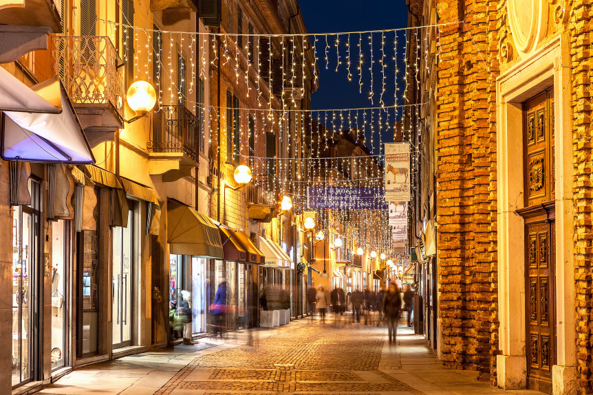 ALBA, ITALY - DECEMBER 30, 2013: Pedestrian street in old town illuminated and decorated for Christmas and New Year holidays. This area is very popular with locals and tourists visiting Alba.