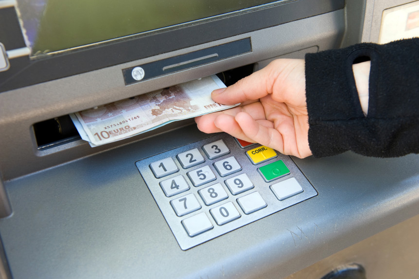 ENSCHEDE NETHERLANDS - APRIL 28: A woman is withdrawing cash money out of an ATM machine APRIL 04 2013 in the Netherlands